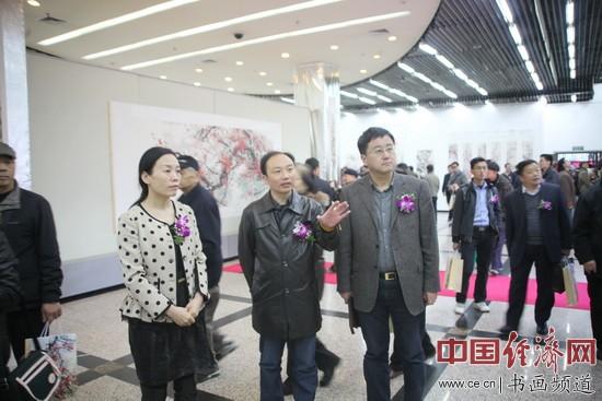 著名彩墨国画家李政恩(中)向领导和嘉宾讲述李俊香国画作品的艺术特色 中国经济网记者李冬阳摄